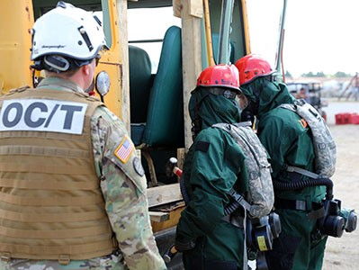 An external evaluator looks on as members of the Wisconsin Chemical Biological Radiological Nuclear Enhanced Response Force Package (CERF-P) conduct a search and extraction mission Aug. 17 at Volk Field, Wis. The CERF-P is evaluated every two years in order to maintain and validate its readiness for a worst-case scenario. Wisconsin National Guard photo by Sgt. Amber Peck