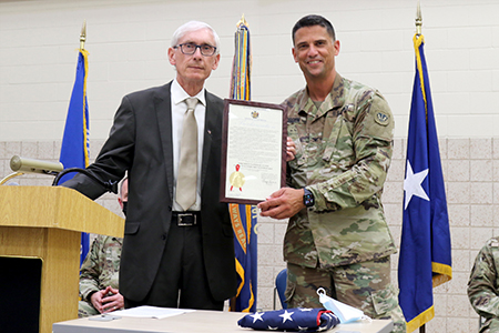 Gov. Tony Evers presents a framed proclamation to Col. John Morgen, commander of Joint Task Force 64, during a ceremony Aug. 24 at the Armed Forces Reserve Center in Madison, Wis., honoring Wisconsin National Guard troops who have supported the state's COVID-19 response efforts since March 2020. Wisconsin Gov. Tony Evers proclaimed Aug. 24, 2021, as Wisconsin National Guard COVID-19 Support Recognition Day, thanking Wisconsin National Guard members for their continued efforts in the state's COVID-19 response efforts. Wisconsin Department of Military Affairs photo by Kelly Bradley