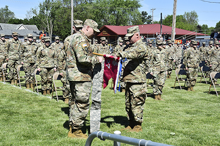 Capt. Shawn Smith, commander of the Wisconsin Army National Guard's 107th Maintenance Company, and unit 1st Sgt. Craig Twinde case the unit guidon — signifying the unit is temporarily leaving the command and control of the Wisconsin Army National Guard — during a formal sendoff ceremony at Sparta Memorial Field in Sparta, Wis., May 29. The 107th is based in Sparta, with detachments in Viroqua, Wis., and Camp Ripley, Minn. The unit is deploying to Eastern Europe to perform maintenance and recovery operations in support of Operation Atlantic Resolve and the Defender-Europe 2021 multinational joint exercise. Wisconsin Department of Military Affairs photo by Vaughn R. Larson