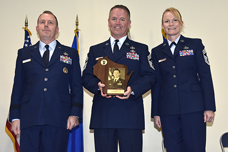 Brig. Gen. David May, Wisconsin's deputy adjutant general for Air, and Chief Master Sgt. Meredith Conn, the Wisconsin Air National Guard's senior enlisted leader, present retired Chief Master Sgt. Gregory Cullen with a plaque during an Aug. 16 Wisconsin Air National Guard Hall of Fame induction ceremony at the 115th Fighter Wing in Madison, Wis. Cullen was the first state command chief to hold the position full-time. He also created the state's first enlisted development program to prepare younger Airmen for advancement. Wisconsin Department of Military Affairs photo by Vaughn R. Larson