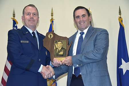 Brig. Gen. David May, Wisconsin's deputy adjutant general for Air, presents retired Col. Christopher Charney with a plaque during an Aug. 16 Wisconsin Air National Guard Hall of Fame induction ceremony at the 115th Fighter Wing in Madison, Wis. Charney was the first Wisconsin Air National Guard officer to serve as joint director of intelligence and security, while simultaneously serving as the Wisconsin Air National Guard's director of intelligence, surveillance and reconnaissance. Wisconsin Department of Military Affairs photo by Vaughn R. Larson